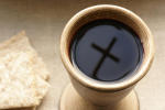 Chalice with wine and bread. Cross shadow in the chalice.
